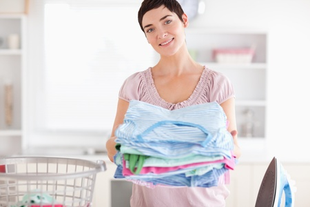 Brunette Woman with a pile of clothes in a utility room photo