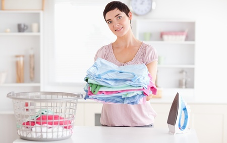Beautiful Woman with a pile of clothes in a utility room photo
