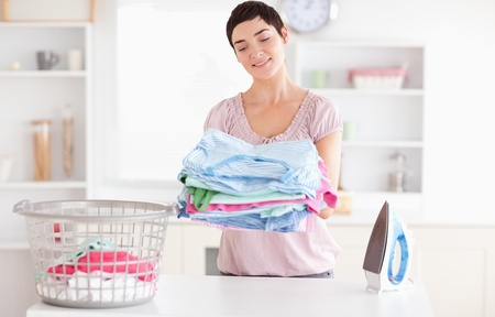 Joyful Woman with a pile of clothes in a utility room photo