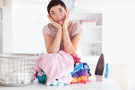 Surprised Woman with a pile of clothes in a utility room photo