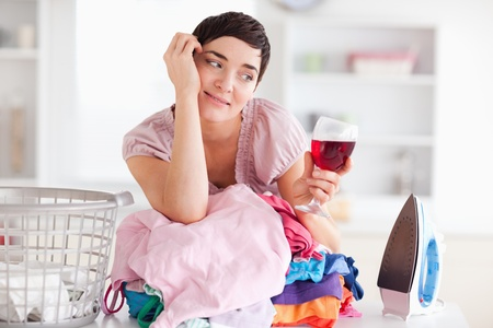 Cute Woman with wine and a pile of clothes in a utility room photo