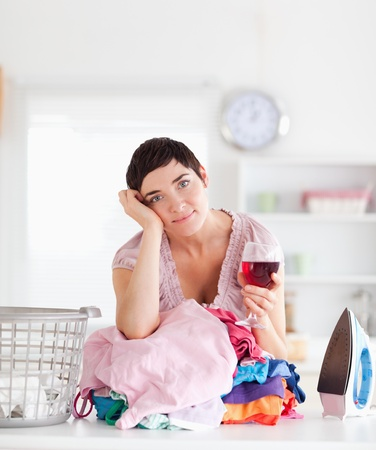 Brunette Woman with wine and a pile of clothes in a utility room photo