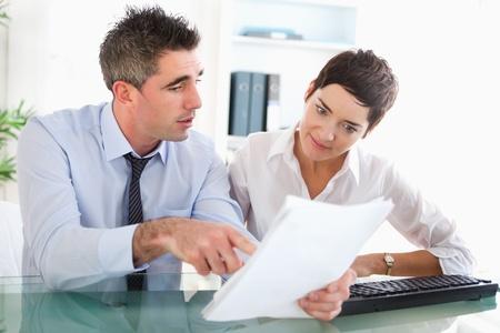 two people talking: Los colegas de lectura de documentos en una oficina