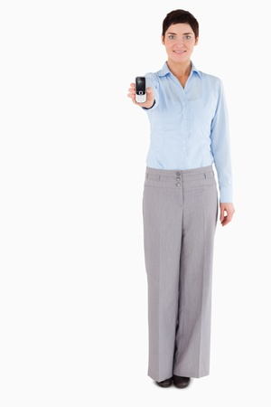 Smiling businesswoman showing a cellphone against a white background Stock Photo - 11227577