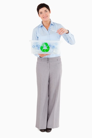 Woman putting a plastic bottle in a recycling box against a white background Stock Photo - 11227892