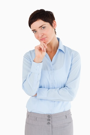 Businesswoman with herhand on her chin against a white background photo