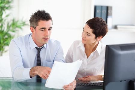 dos personas conversando: Compa�eros de trabajo mirando a un documento en una oficina