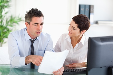 two people talking: Coworkers looking at a document in an office