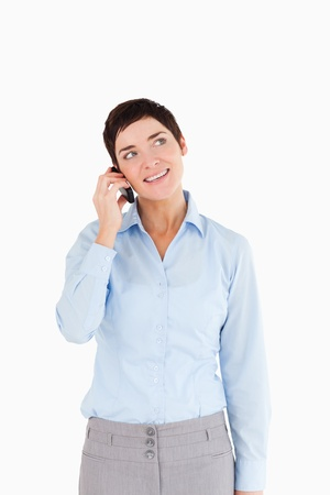 Portrait of a businesswoman answering the phone against a white background photo