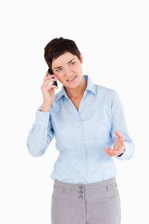Portrait of a angry woman on the phone against a white background photo