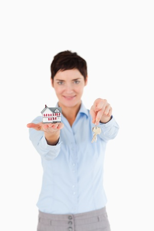 Woman showing keys and a miniature house against a white background photo