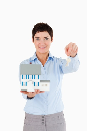 Real estate agent holding keys and a miniature house against a white background photo