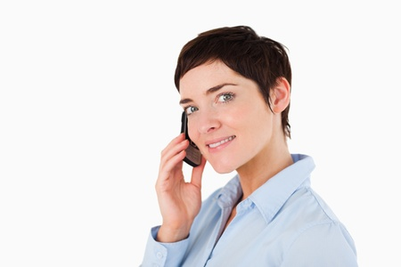 Close up of a serious woman on the phone against a white background photo