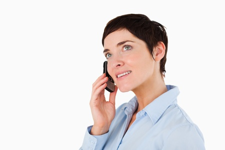 Close up of a serious woman making a phone call against a white background photo