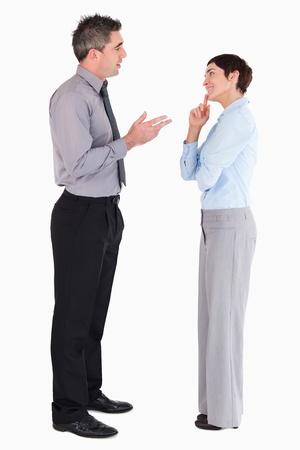 dos personas platicando: Los gerentes que hablan el uno al otro sobre un fondo blanco