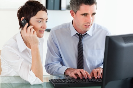 Woman telephoning while her colleague is using a computer in an office photo