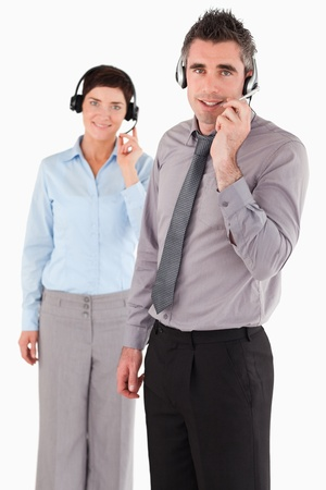 telephone saleswoman: Portrait of office workers using headsets against a white background