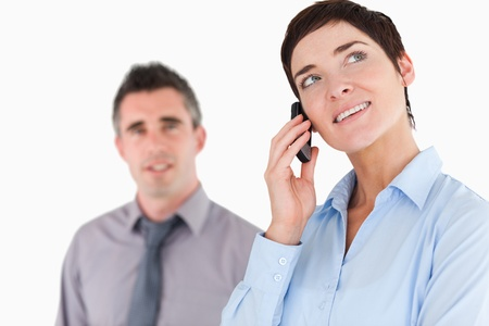 Woman making a phone call while her colleague is posing against a white background photo
