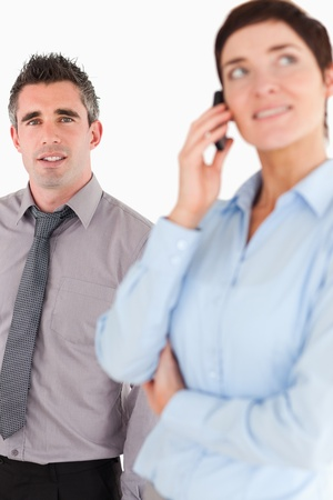 Portrait of a woman on the phone call while her coworker is posing against a white background photo
