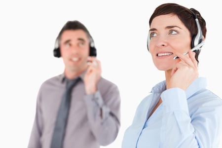 Close up of colleagues using headsets against a white background photo