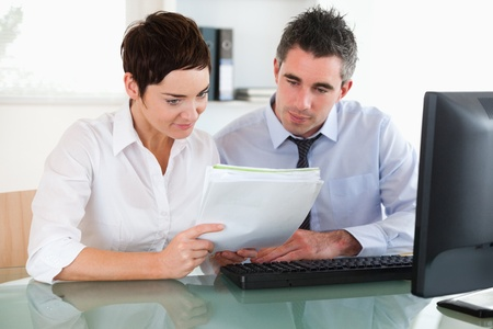 Female and male workers looking at a document in an office Stock Photo - 11187252