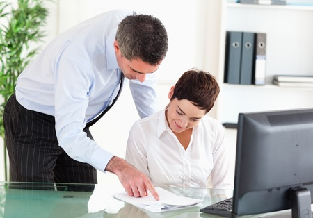 Business manager showing something on a document to his secretary in an office Stock Photo - 11189700