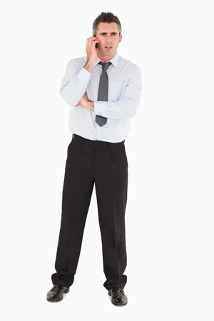 Angry businessman using a mobile phone against a white background photo