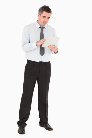 Smiling businessman using a tablet computer against a white background photo