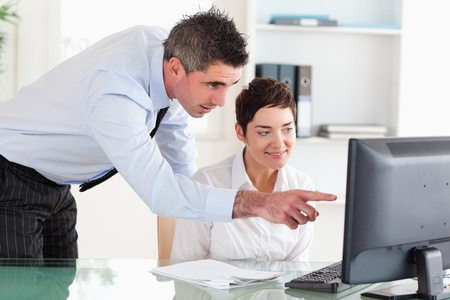 Businessman pointing at something on a screen to his secretary in an office photo