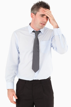 Portrait of a sad businessman with his hand on his forehead against a white background photo