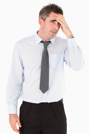 Portrait of a sad business manager with his hand on his forehead against a white background photo