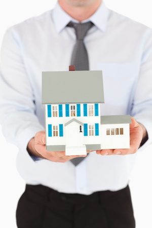 Portrait of a man holding a miniature house against a white background photo