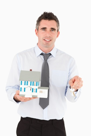 Man holding a key and a miniature house against a white background photo