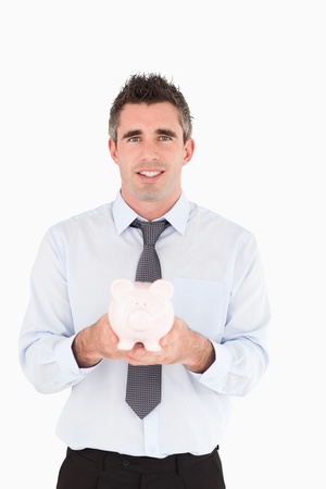 Man showing a piggy bank against a white background photo