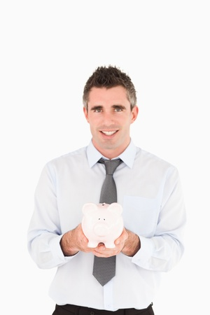 Portrait of a businessman showing a piggy bank against a white background Stock Photo - 11227806
