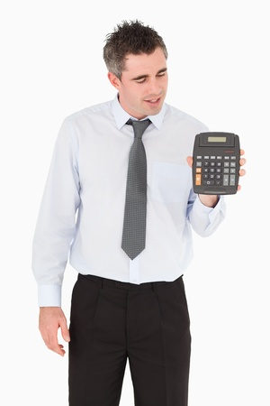 Accountant looking at a calculator against a white background photo