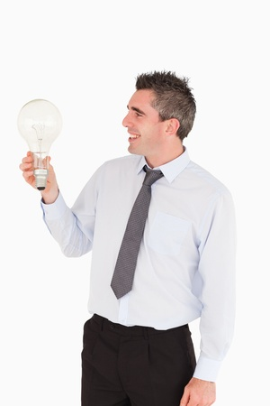 Man looking at a light bulb against a white background photo