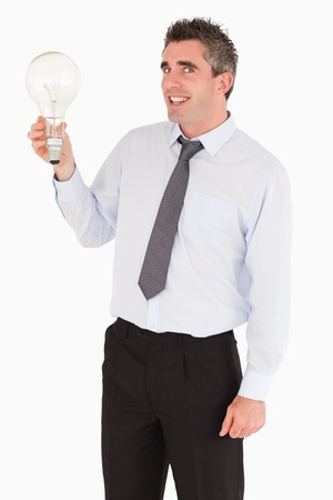Smiling man holding a light bulb against a white background photo