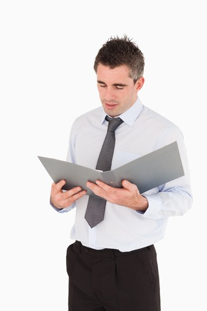 Portrait of a man looking at a binder against a white background photo
