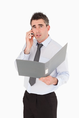 Portrait of a man making a phone call while holding a binder against a white background photo