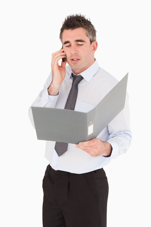 Portrait of a businessman making a phone call while holding a binder against a white background photo