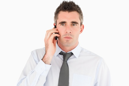 Unhappy man making a phone call against a white background photo