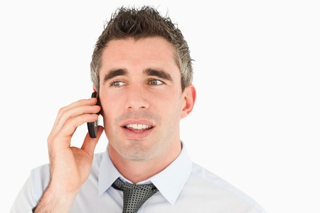 Close up of a businessman making a phone call against a white background photo