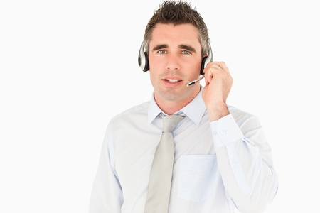 Male secretary speaking through a headset against a white background photo