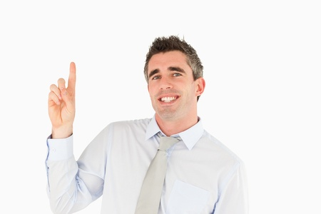 Smiling businessman pointing at copy space against a white background photo