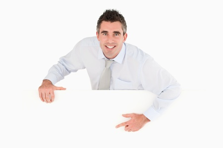 Businessman pointing at blank panel against a white background Stock Photo - 11227560