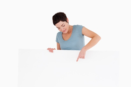 Brunette woman pointing at something on a panel against a white background photo