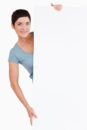 Woman posing behind a blank panel against a white background Stock Photo - 11228291