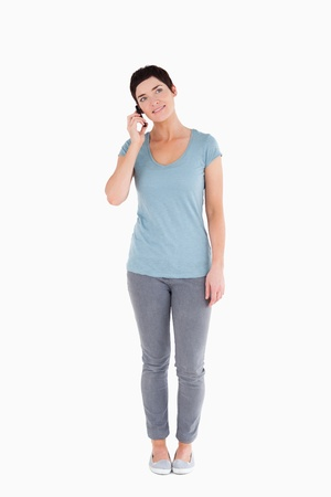 Dark-haired woman answering the phone against a white background Stock Photo - 11227775