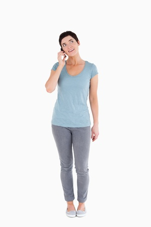 Smiling woman answering the phone against a white background Stock Photo - 11227648